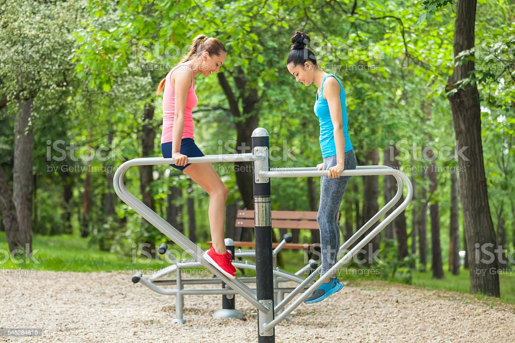 Smiling young women making push-ups on parallel bars stock photo