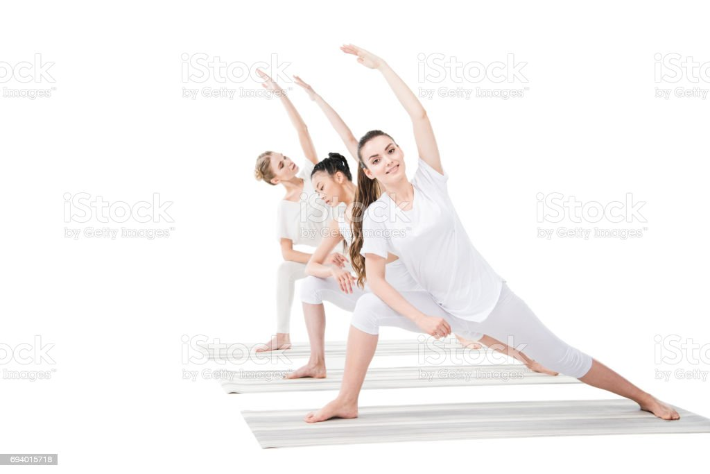 Smiling young women practicing Extended Side Angle Pose on yoga mats stock photo