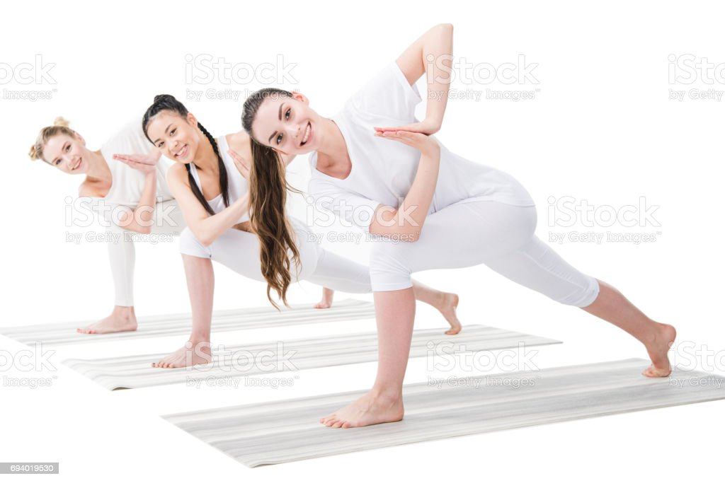 Smiling young women practicing variation of Revolved Side Angle Pose (Parivrtta Parsvakonasana) stock photo