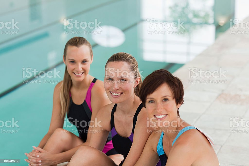 Smiling young women sitting at edge of swimming pool royalty-free stock photo