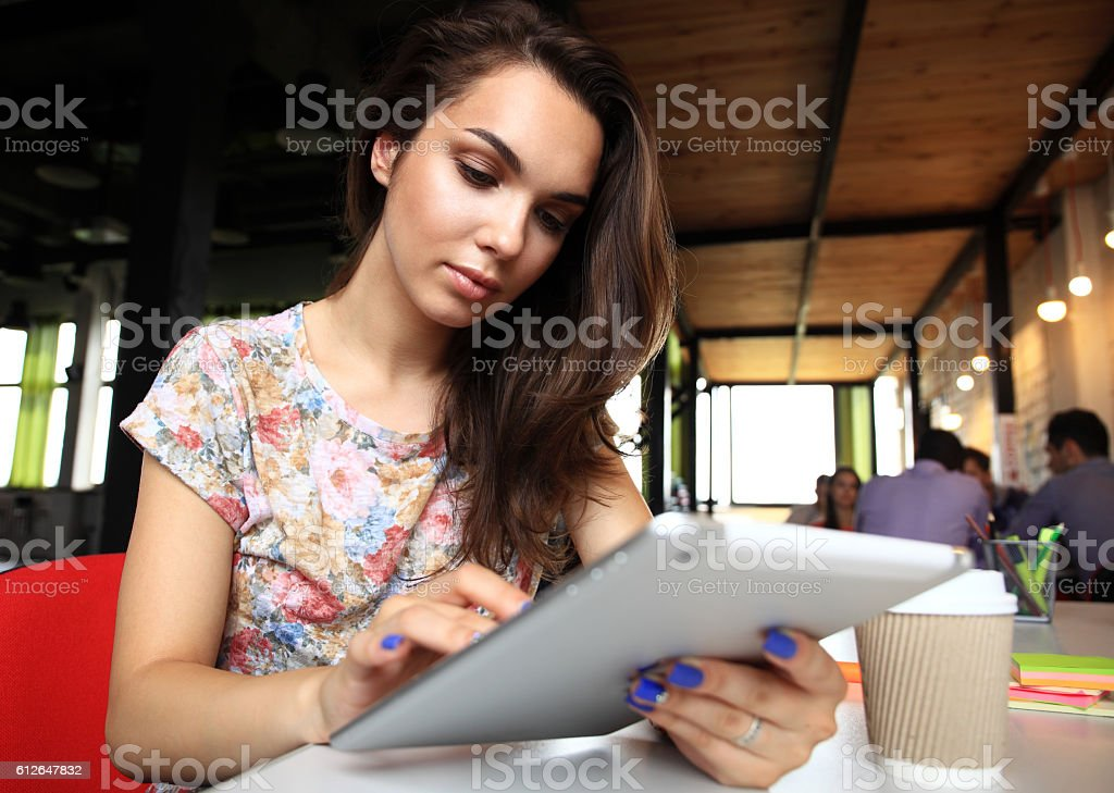 Smiling young women using digital tablet in office stock photo