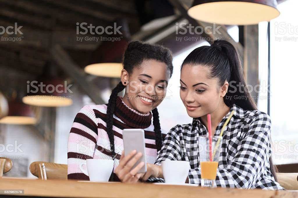Smiling young women using phone in a bar stock photo