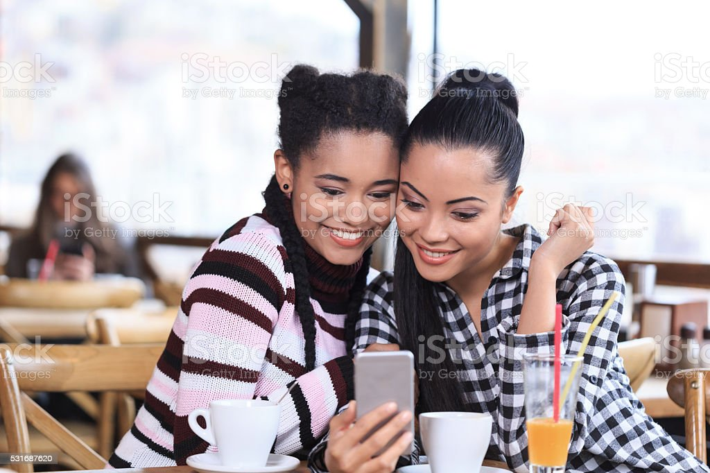 Smiling young women using phone in a restaurant stock photo