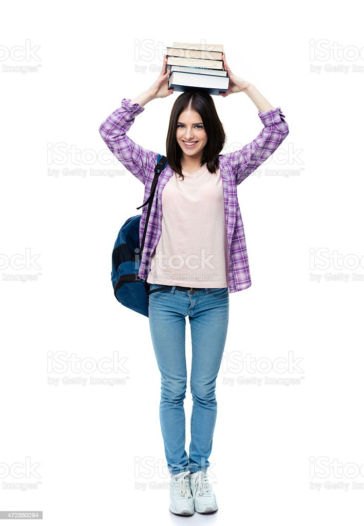 Smiling young wowan holding books on head stock photo