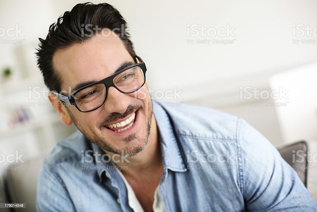Smilling man with eyeglasses sitting in sofa royalty-free stock photo