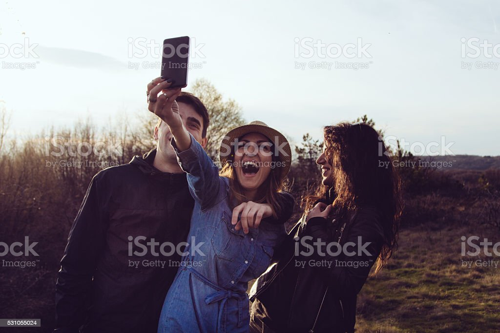 Smilling three young people laughing at phone' camera stock photo