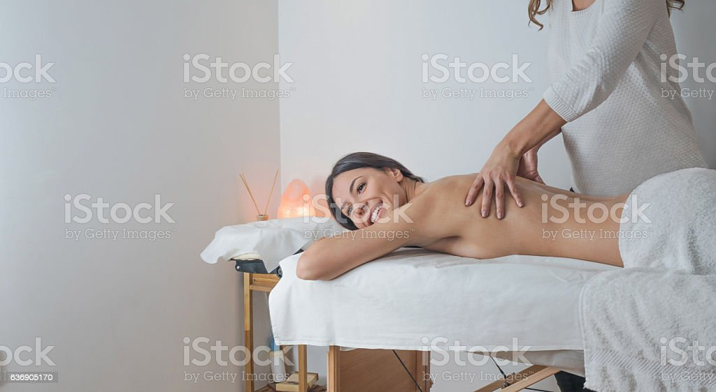 Smilling young brunette woman receiving back massage stock photo