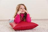 Smirking little girl lying at red cushion