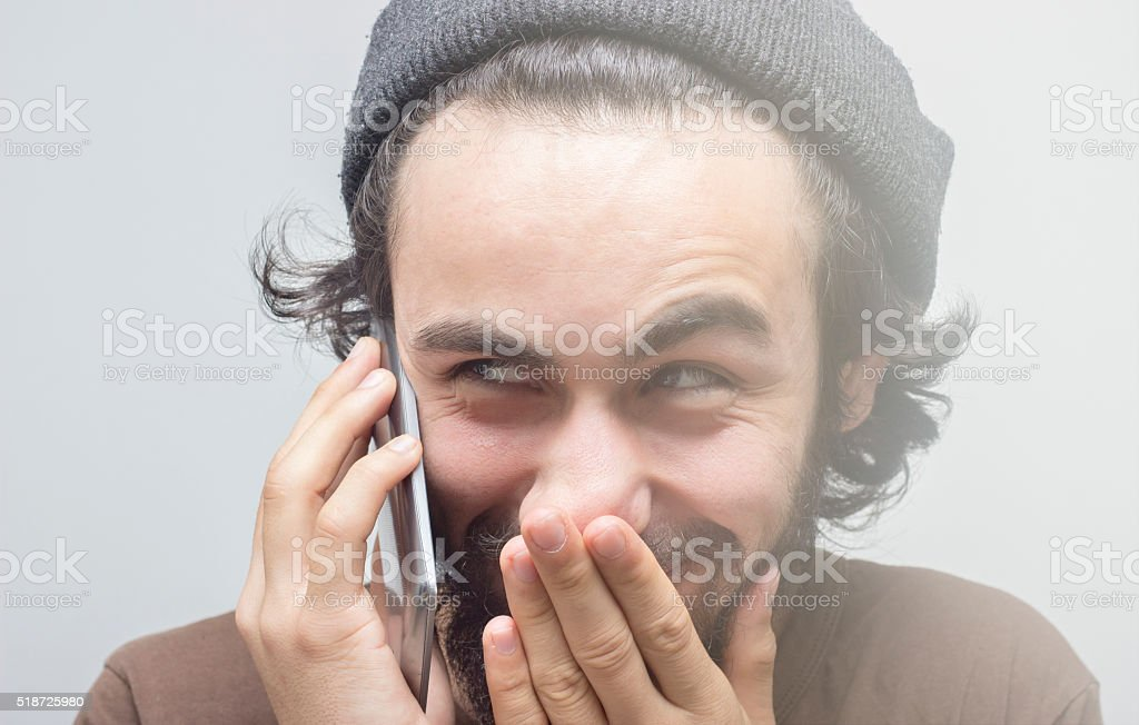 Smirking young man talking on phone over gray background stock photo