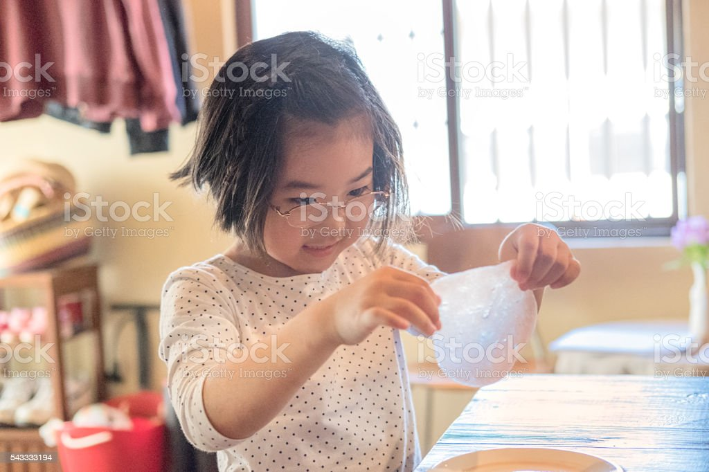 Smling Japanese Girl Examining Slime Science Experiment at Home stock photo