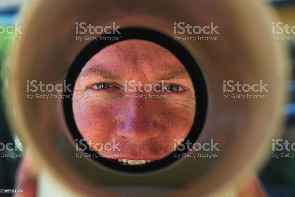 Smling plumber looking down drain pipe royalty-free stock photo