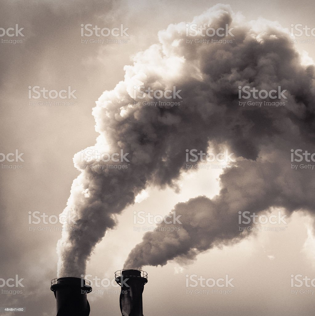 Smoke billowing from industrial chimneys stock photo