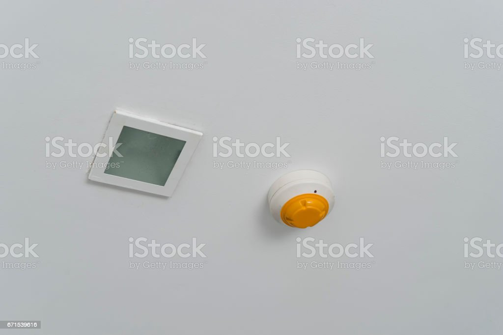 smoke detector and emergency light on ceiling stock photo