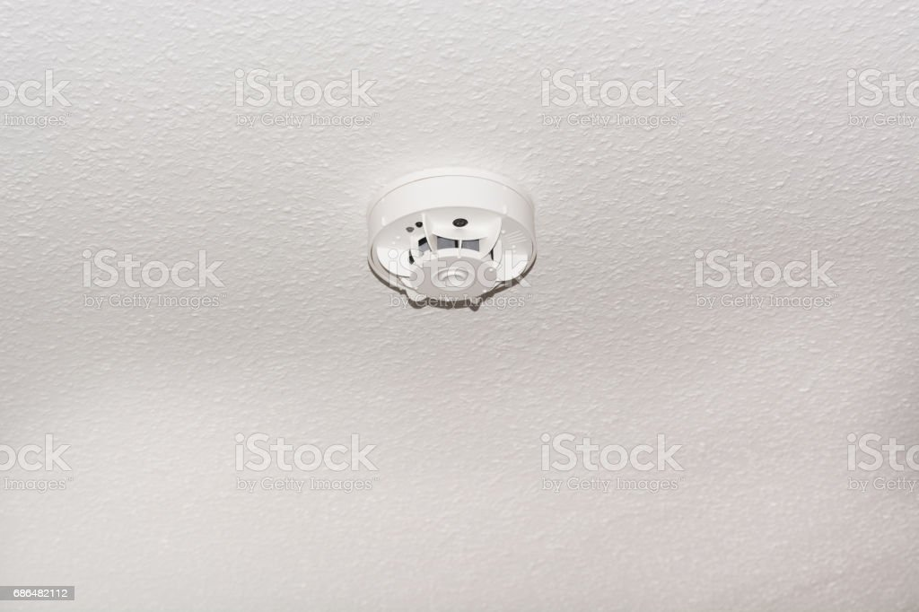 Smoke detector on the ceiling and smoke. stock photo