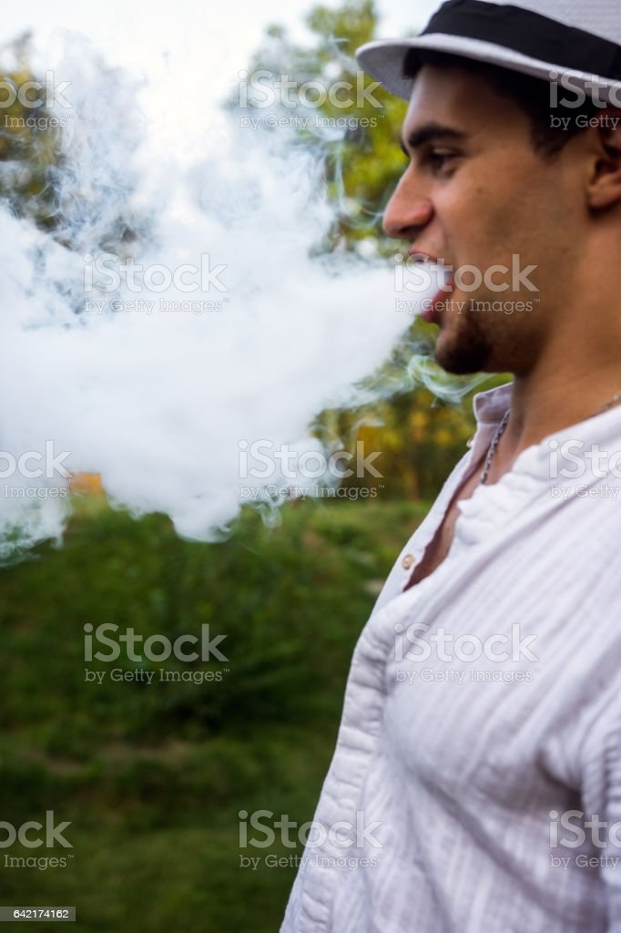 Smoke exhaled by young men stock photo