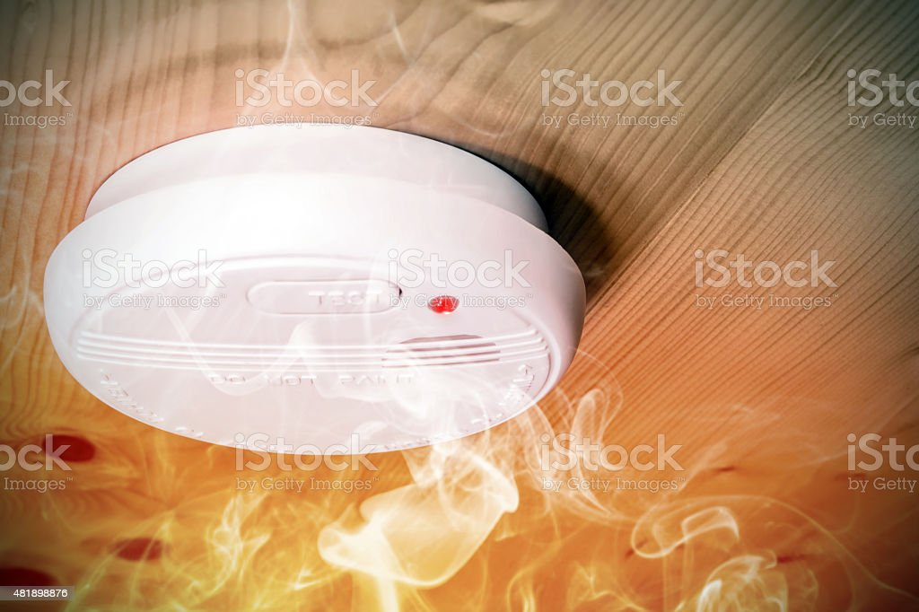 Smoke fire detected by home smoke detector alarm on ceiling stock photo