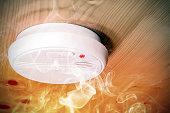 Smoke fire detected by home smoke detector alarm on ceiling