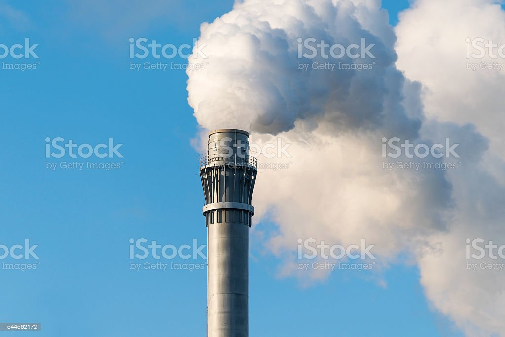 smoke from an industrial chimney against the blue sky stock photo