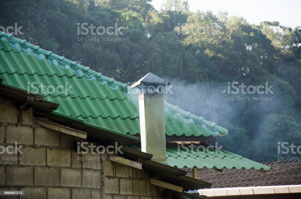 Smoke from chimney of local house in morning time stock photo