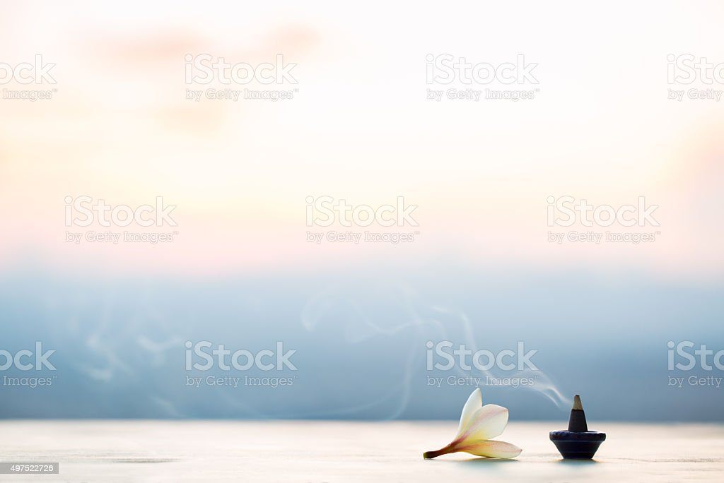 Smoke incense cones with plumeria flower on sunset stock photo