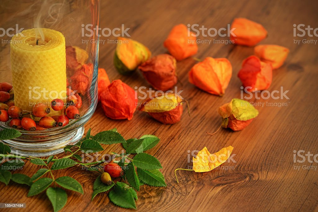 smoke of beeswax Candle in glass with rose hips stock photo
