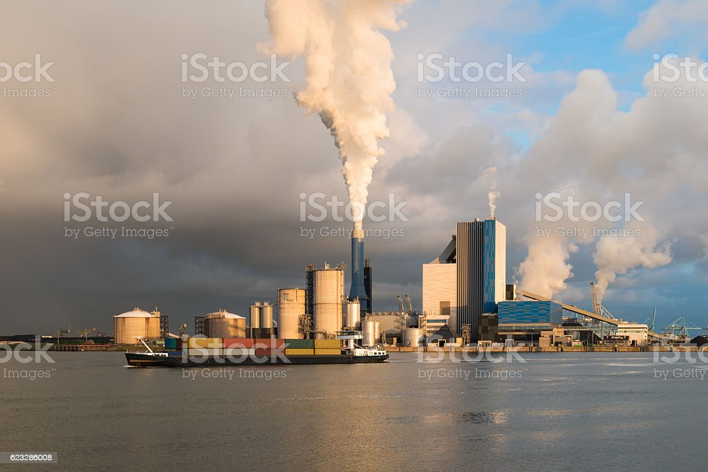 Smoke of heavy industry is highlighted by the sun. stock photo