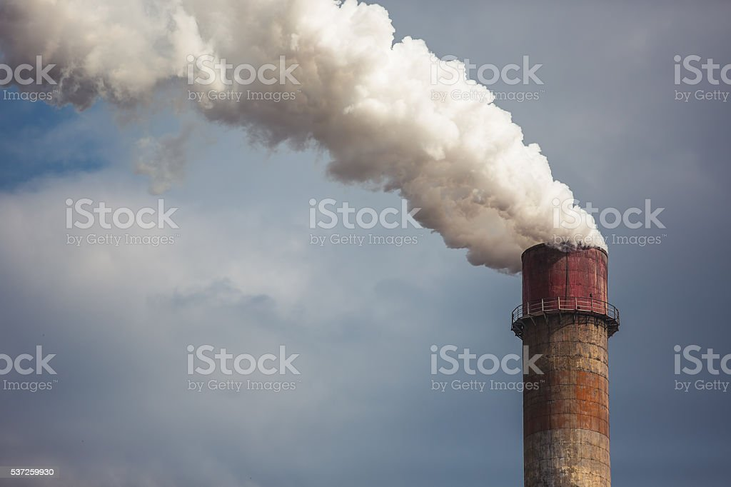 Smoke rising from an industrial chimney stock photo
