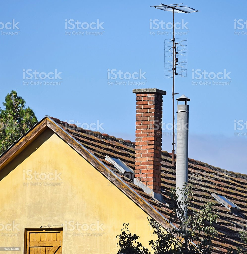 Smoke stacks and antennas on the roof stock photo