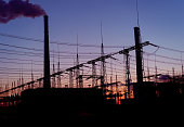 Smoke stacks at coal burning power plant, industrial silhouette.