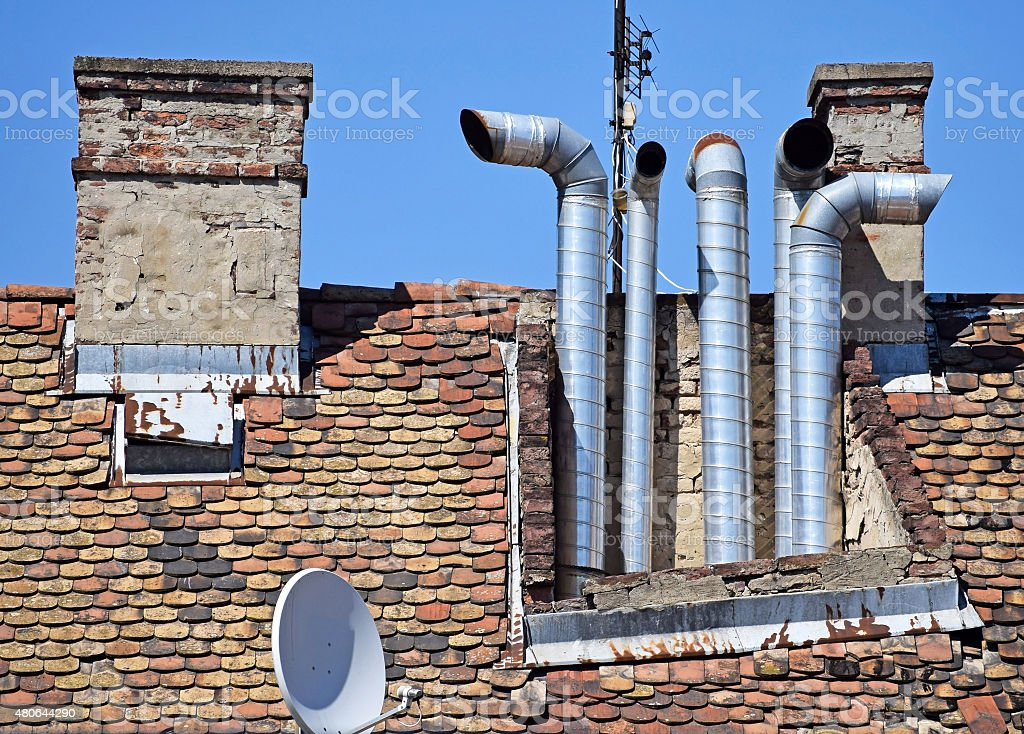 Smoke stacks on the roof of a building stock photo