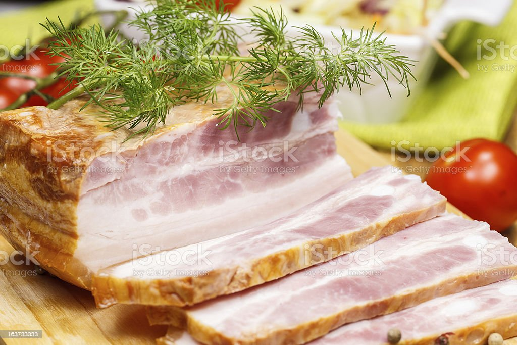 Smoked bacon and spices on cutting board royalty-free stock photo