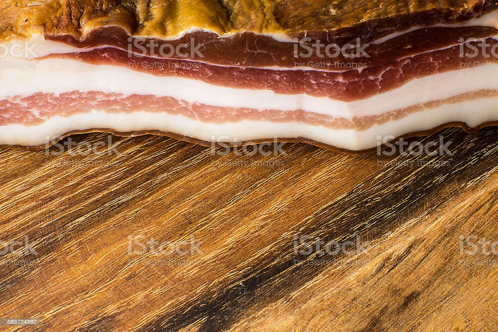 Smoked bacon on vintage wooden board stock photo
