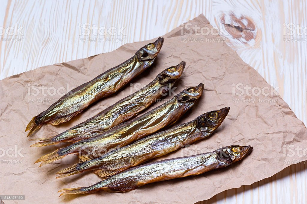 Smoked  capelin on vintage wooden background, top view stock photo