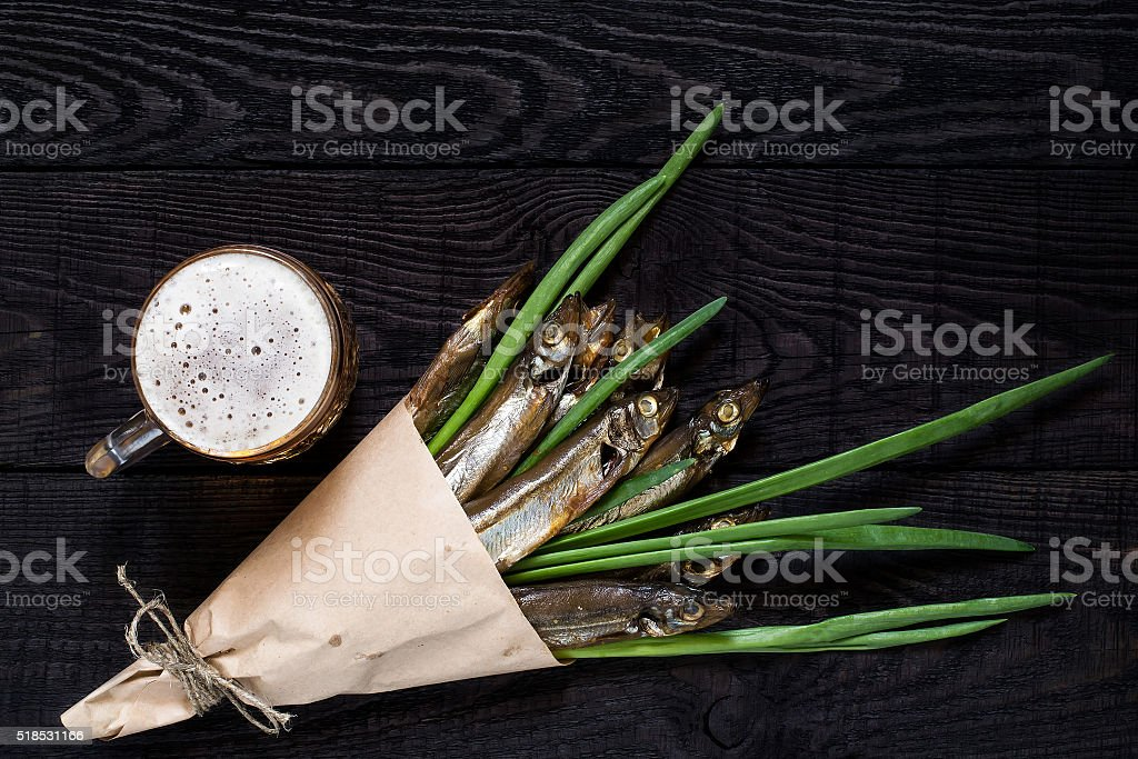 Smoked capelin with green onions and beer stock photo