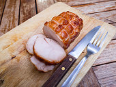 Smoked chicken breast wooden cutting board with fork and knife