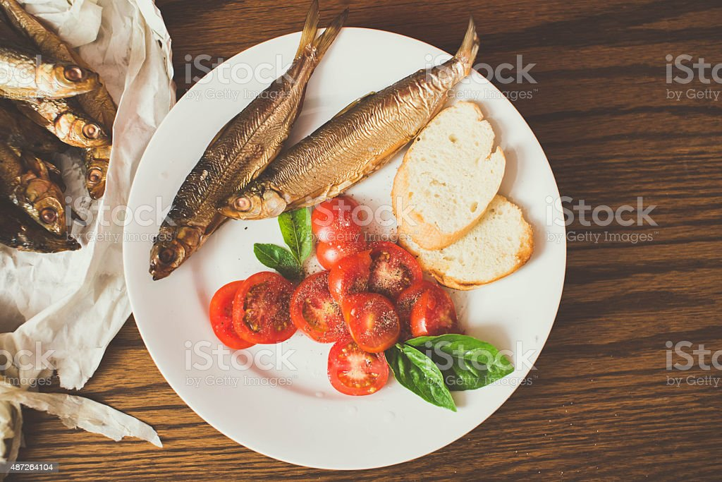 smoked fish on paper, wooden table, pepper mill stock photo