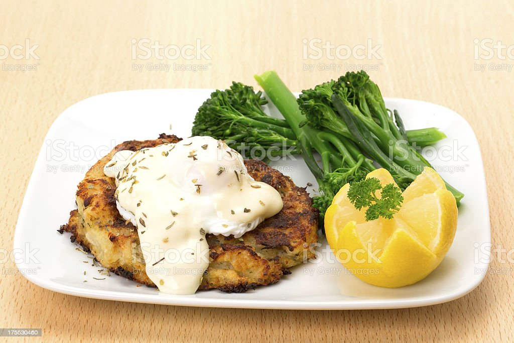 Smoked haddock fishcake dinner with a poached egg stock photo