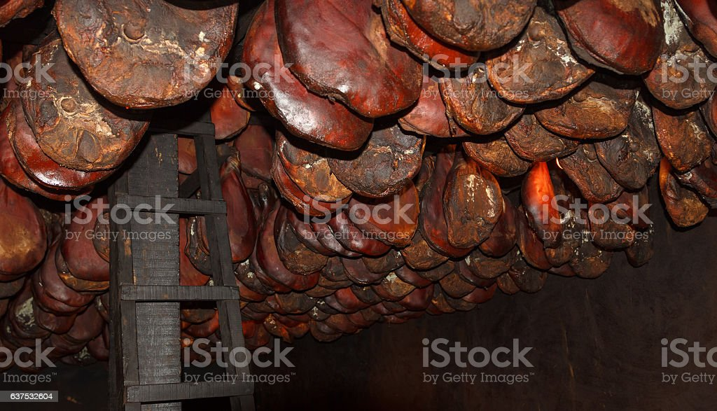 Smoked hams of prosciutto hanging at factory in Montenegro stock photo