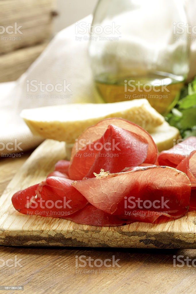Smoked meat bresaola on a cutting board royalty-free stock photo