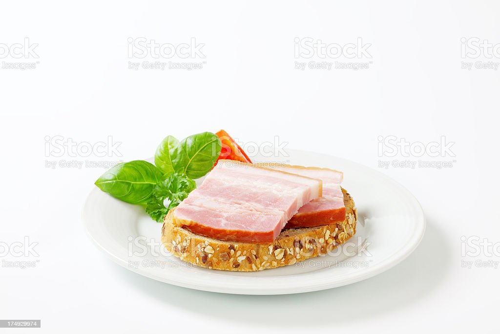 Smoked pork bacon on a slice of bread royalty-free stock photo