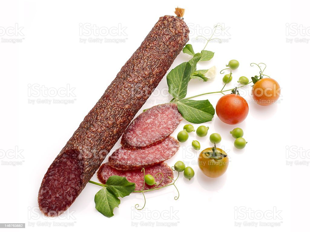 Smoked salami decorated with tomatoes and green pea royalty-free stock photo
