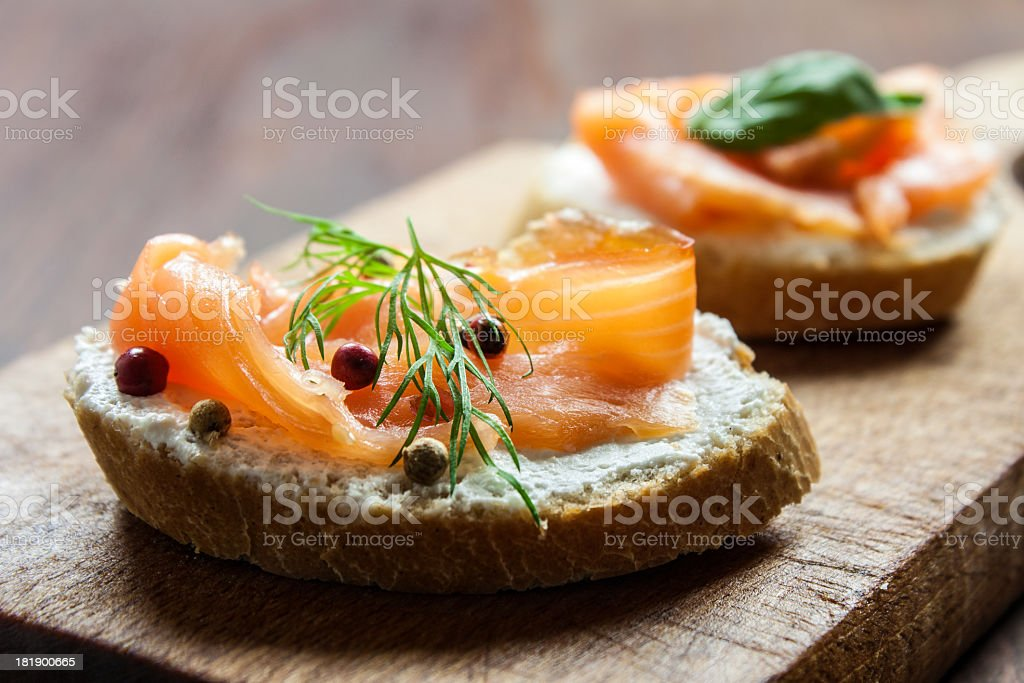 Smoked salmon canapes on a brown wooden plate stock photo