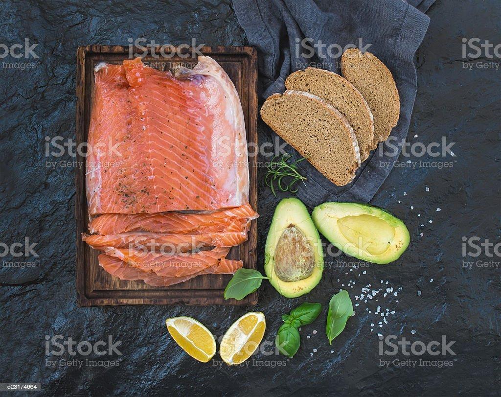 Smoked salmon filet with lemon, avocado, fresh herbs and bred stock photo
