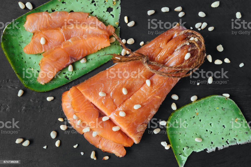 Smoked salmon fish on a slate board. Top view at cutted slices of smoked salmon on a slice of a green pesto cheese. Pine nuts scattered over salmon fish and cheese. stock photo