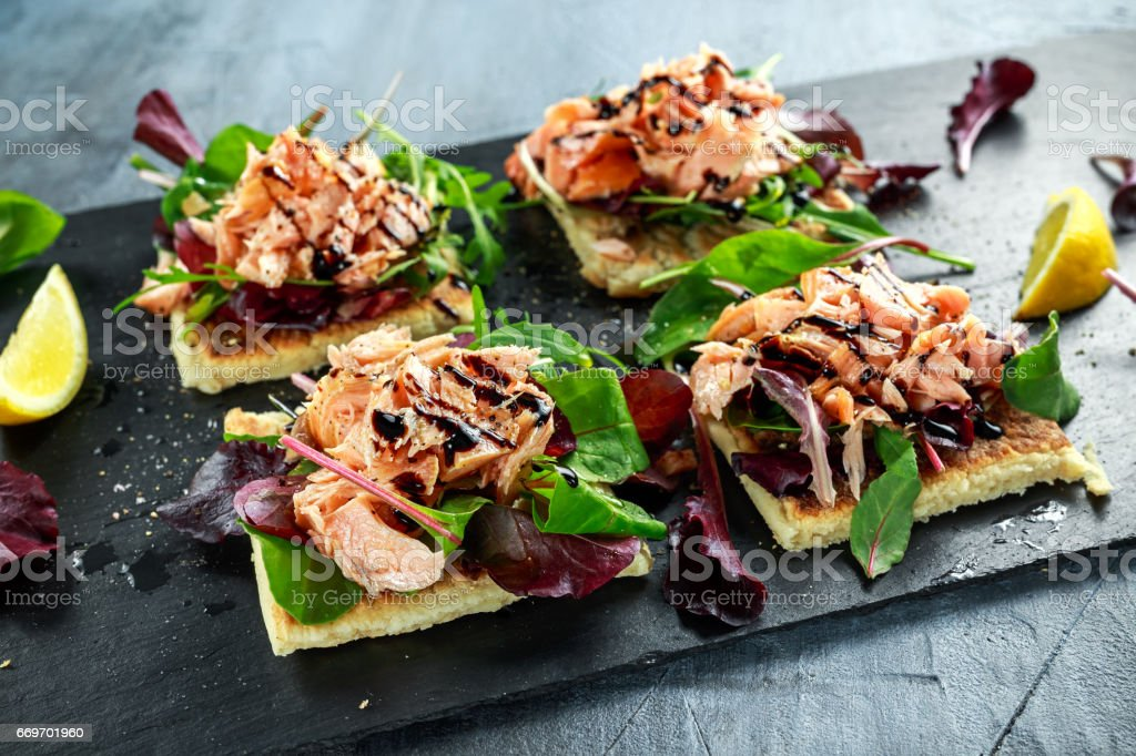 Smoked salmon flakes on salad bed and irish potato slims snacks, appetizers stock photo