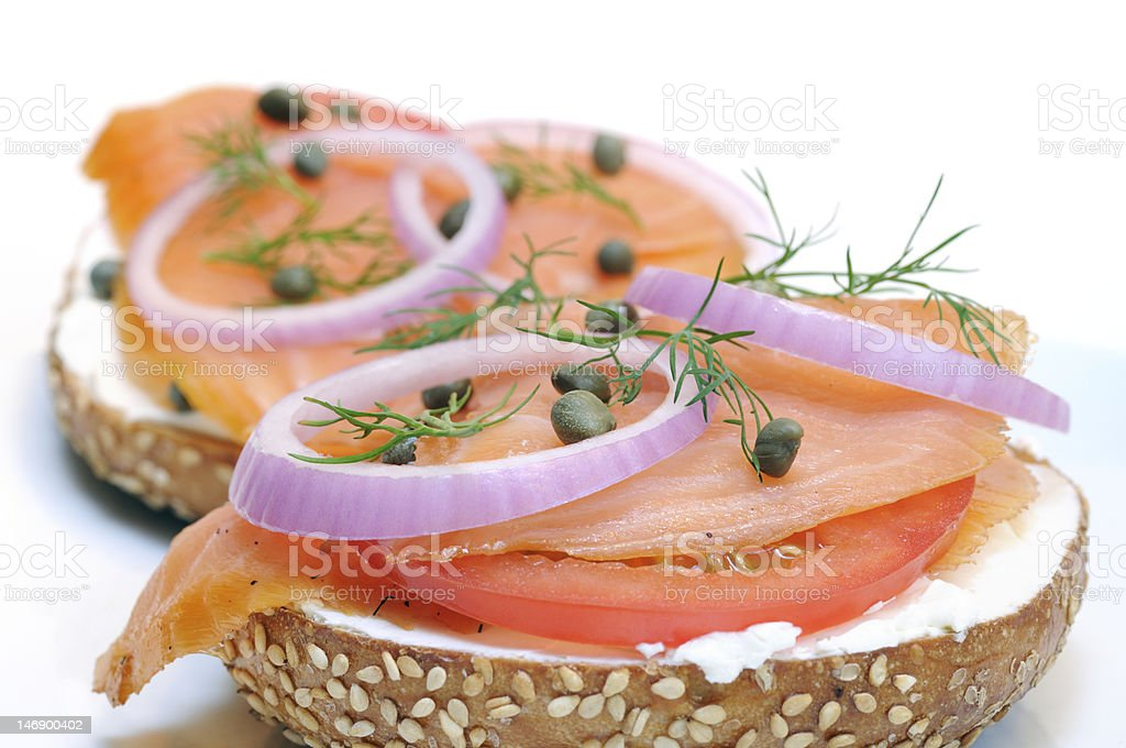 Smoked salmon with red onion and capers on a sesame bagel stock photo