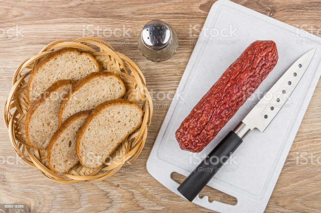 Smoked sausage on cutting board and bread in wicker basket stock photo