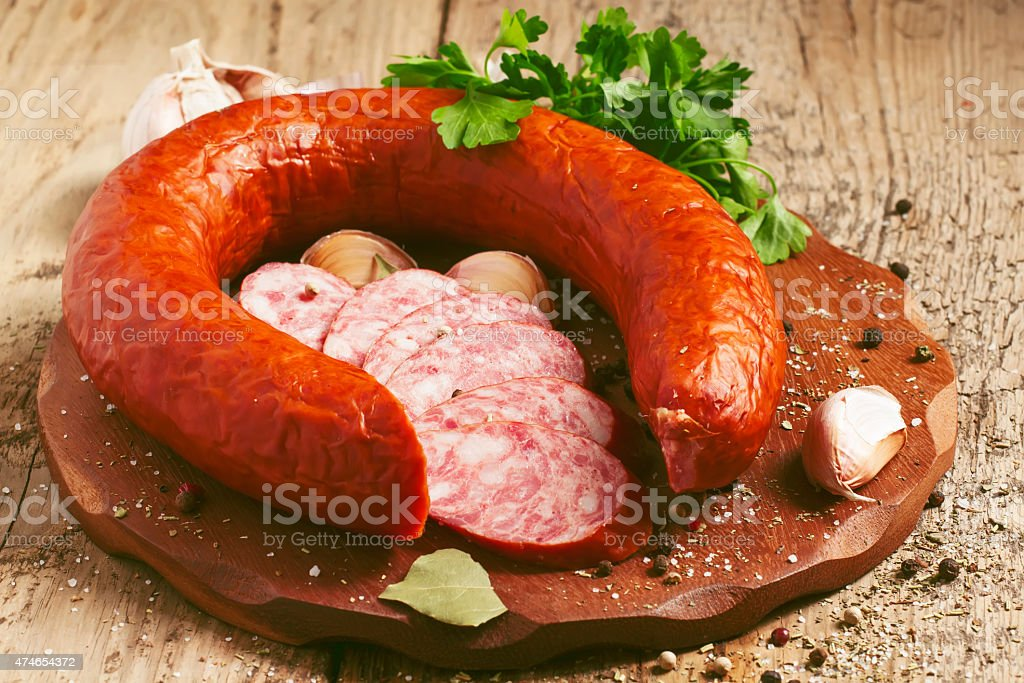 Smoked sausage ring with spices and herbs in rustic style stock photo
