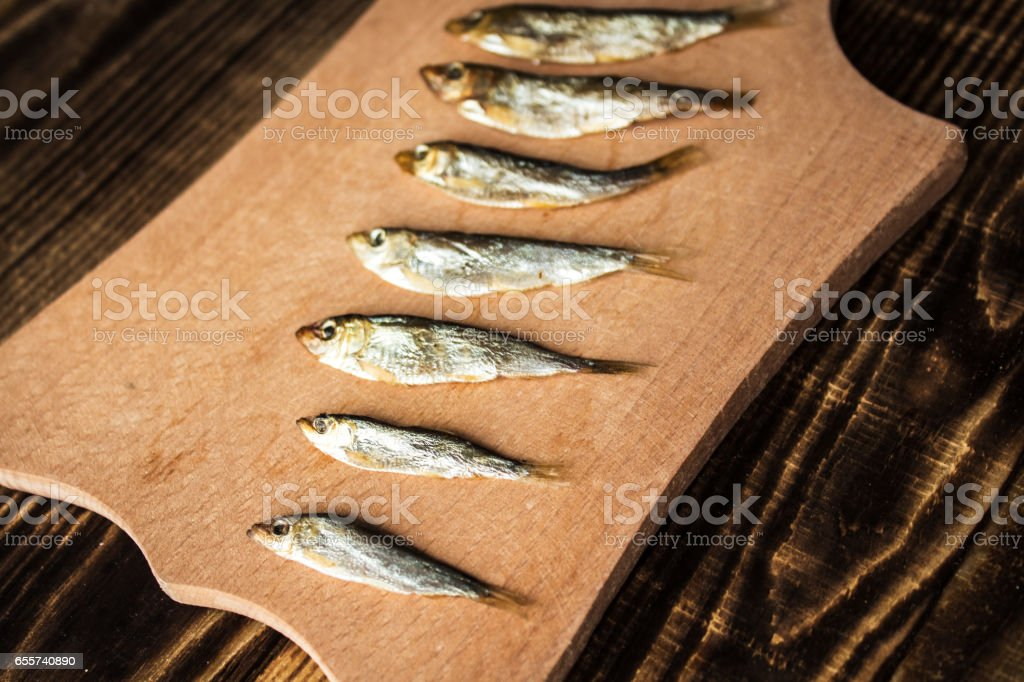 smoked sprats on wooden background stock photo