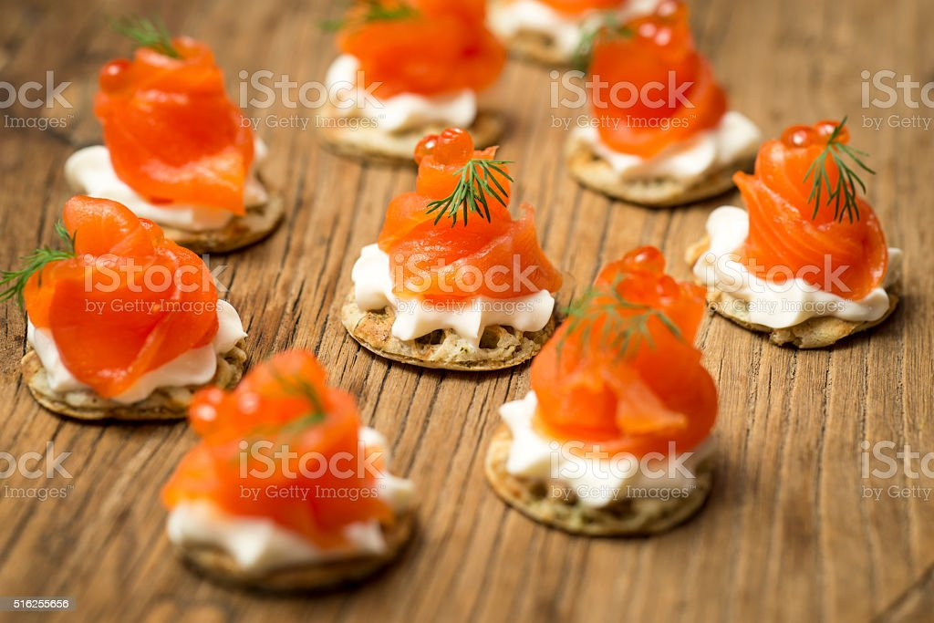 Smoked Trout Blinis on a wooden board stock photo